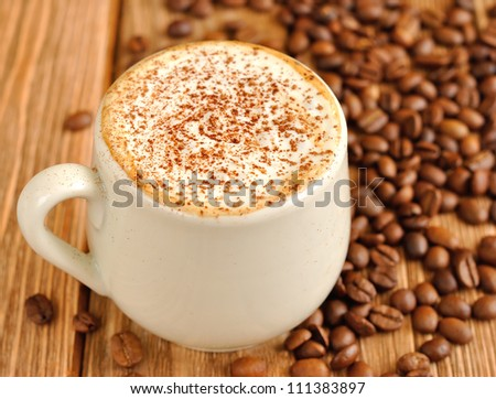 Coffee with froth and coffee beans - stock photo