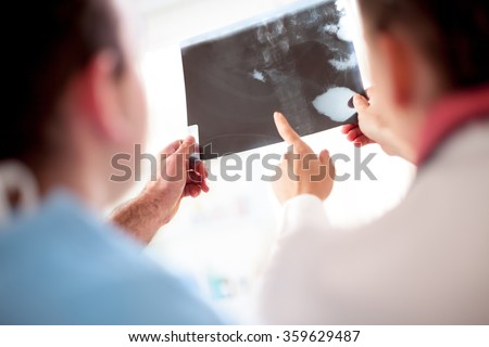colleagues doctors exchanged opinions looking at x-ray or roentgen image - stock photo