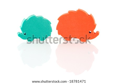 2 colored hedgehogs (foam plastic silhouettes) with reflections, white background - stock photo