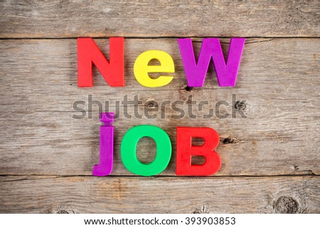 Colored Letter magnets spelling text NEW JOB - stock photo