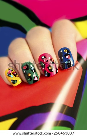 Colored nail Polish on a woman's nails with rhinestones and design points. - stock photo