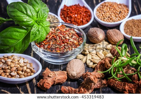 Colorful aromatic spices and herbs on an old oak wooden brown backgrownd - stock photo