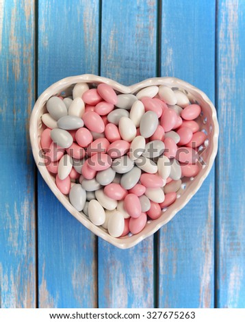 Colorful candy in white heart shaped bowl on wooden table .Top view from above - stock photo