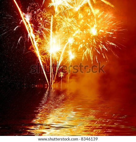 Colorful fireworks reflection in water - stock photo