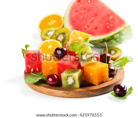 Colorful fruit salad (watermelon, kiwi, orange, cherry) with mint leaves on a  wooden plate isolated on a white background. - stock photo