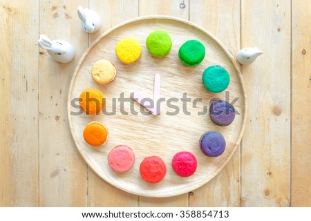 12 Colorful Macarons on the wooden plate , replica as a clock on the Wooden Table, Top View - stock photo