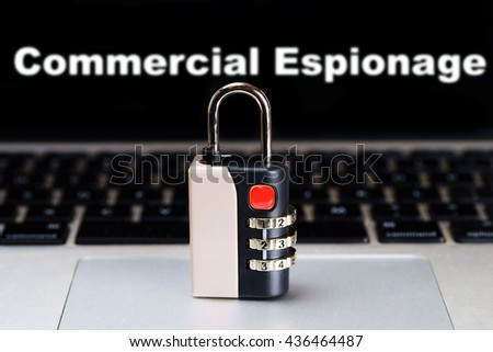 """Commercial Espionage"" text blur on laptop screen with Padlock on a laptop - Internet, web safety, privacy and security concept - stock photo"