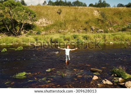 Concept of freedom. Man standing in the lake with open hands - stock photo