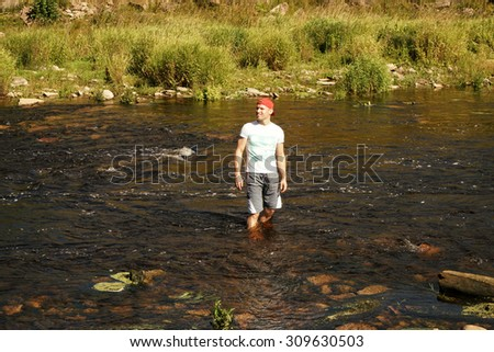 Concept of freedom.Man standing in the river, feels joy  - stock photo