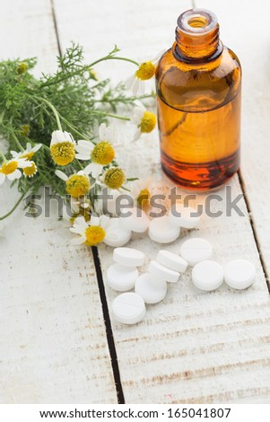 Concept of homeopathy. Bottle with medicines, pills, chamomile. Selective focus. - stock photo