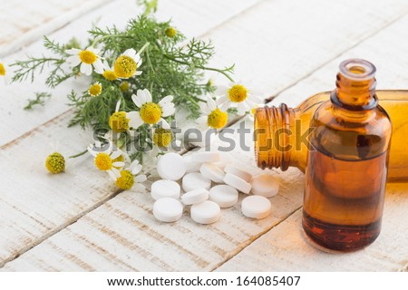 Concept of homeopathy. Bottles with medicines and chamomile flowers. Selective focus. - stock photo
