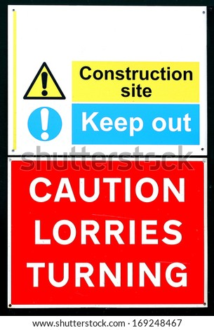 Construction keep out sign and lorries turning - stock photo