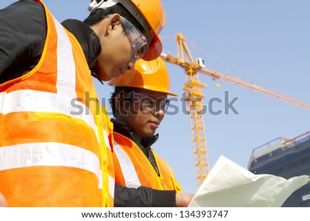 construction workers  discussion on location site with crane in background - stock photo