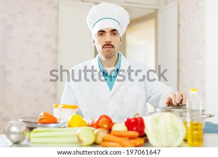 cook man cooking vegetarian lunch at kitchen - stock photo