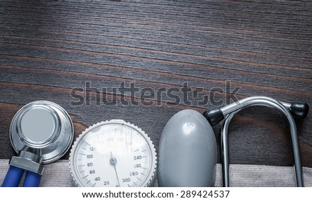 Copy space image of stethoscope and blood pressure monitor on vintage wooden board medicine concept - stock photo