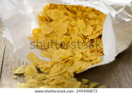 corn flakes on wooden table - stock photo