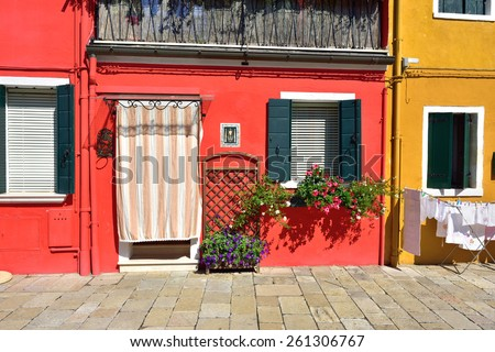 Courtyard with flowers between colorful houses on the famous island Burano, Venice. Venice and the Venetian lagoon are on the UNESCO World Heritage List  - stock photo