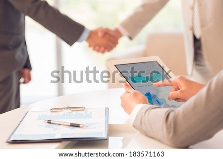 Cropped image of a businessperson making analysis of business report on the foreground while partners handshaking on background  - stock photo