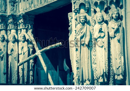 Cross and the entrance to the cathedral of Chartres (France) at background. Selective focus on the figures of saints. Retro aged photo. - stock photo