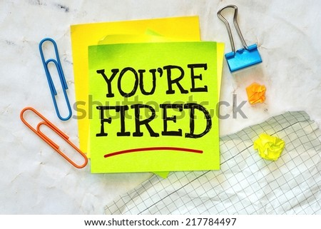 Crumpled paper texture with Business short message text You're fired on the short note notepaper - stock photo