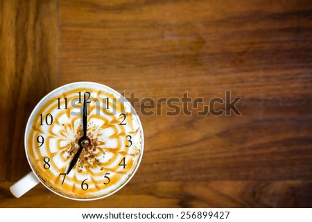 cup of fresh cappuccino with clock sign, view from above  - stock photo