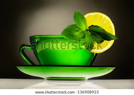 Cup of green tea with spearmint and lemon on dark background - stock photo