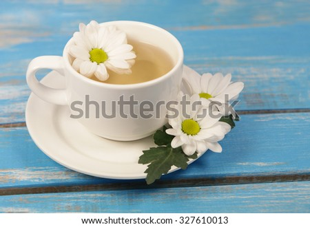 Cup of soothing chamomile tea on rustic wooden  table  background  - stock photo