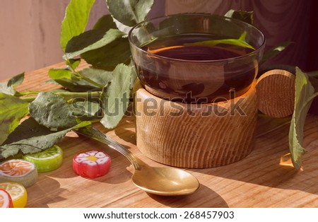 Cup of tea,lollipops,green leaves.On a wooden table. - stock photo