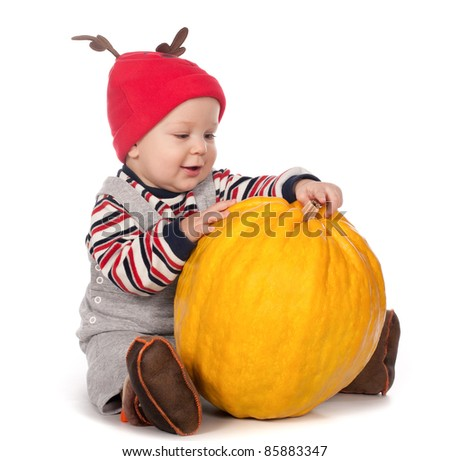 cute baby boy in funny deer hat with orange pumpkin on white background - stock photo