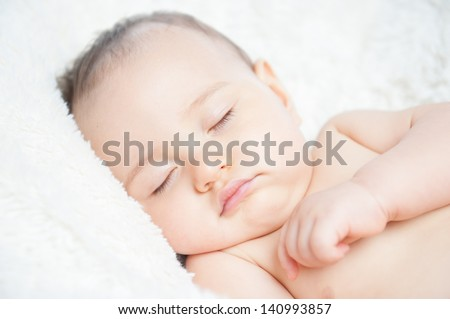 Cute baby sleeping on a blanket - stock photo