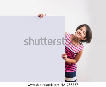 Cute Indian little girl presents with a blank white board, little asian girl presenting white board with copy space - stock photo
