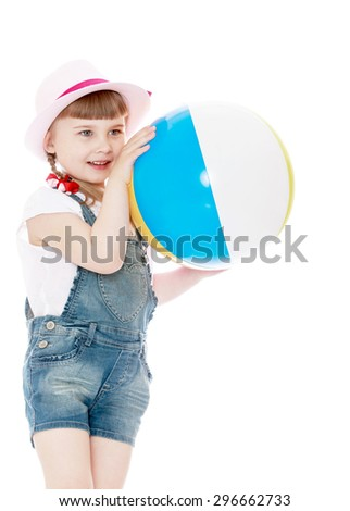 Cute little blond girl in a pink hat and denim shorts happily holding a large inflatable striped ball , girl playing with family on the beach- isolated on white background - stock photo