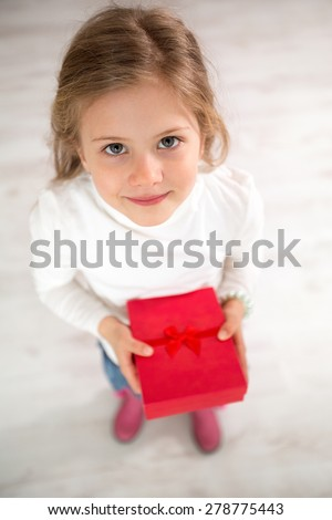 Cute little girl with gift, top view , holidays, presents, birthday concept  - stock photo