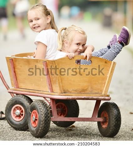 2 Cute little girls in a cart  - stock photo