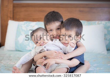 3 cute mixed race Asian Caucasian brothers play happily together inside on a bed - stock photo