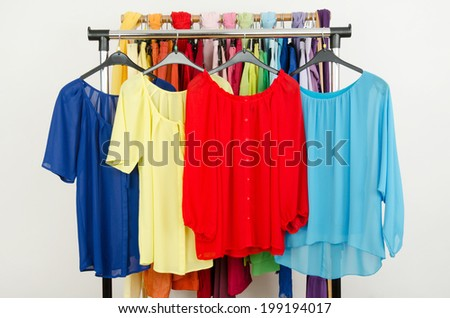 Cute red, yellow, blue blouses displayed on a rack. Wardrobe with colorful summer clothes and accessories. - stock photo