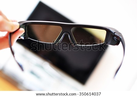 3d-glasses in the hand against TV-set - stock photo