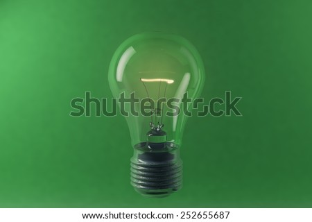 3D illustration of lighting electric bulb on the green background - stock photo
