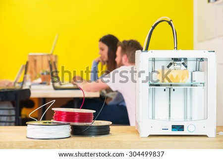 3D printing machine with product on counter with designers discussing in background at creative studio - stock photo