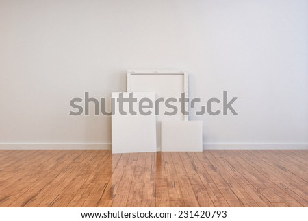 3D Rendering of Three blank canvases and frames on a polished wooden parquet floor in an otherwise unfurnished room interior with a white wall ready for your imagination and interior decor - stock photo
