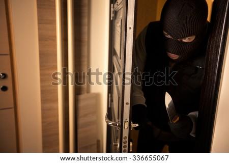 Danger burglar breaks into a apartment - stock photo