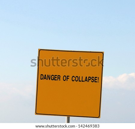 Danger  of collapse!  A sign on the edge of a hill overlooking the sea: The sign warns: Danger, Stay Back, Unstable Cliffs,  Keep Out - stock photo