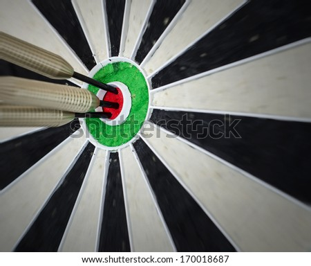 3 darts in the bullseye on a dart board - stock photo