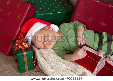 18 days old baby sleeping with christmas presents - stock photo