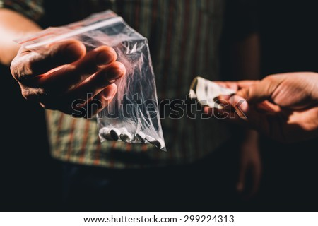 Dealer selling cocaine,ecstasy or other illegal drugs  - stock photo