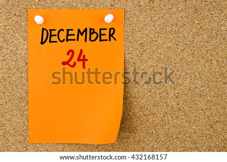 24 DECEMBER written on orange paper note pinned on cork board with white thumbtacks, copy space available - stock photo