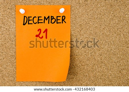 21 DECEMBER written on orange paper note pinned on cork board with white thumbtacks, copy space available - stock photo