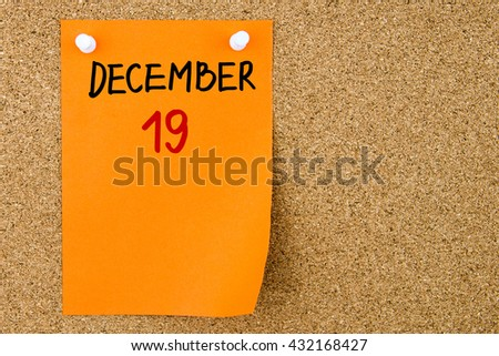 19 DECEMBER written on orange paper note pinned on cork board with white thumbtacks, copy space available - stock photo