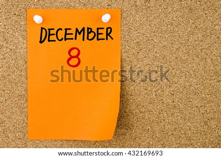 8 DECEMBER written on orange paper note pinned on cork board with white thumbtacks, copy space available - stock photo