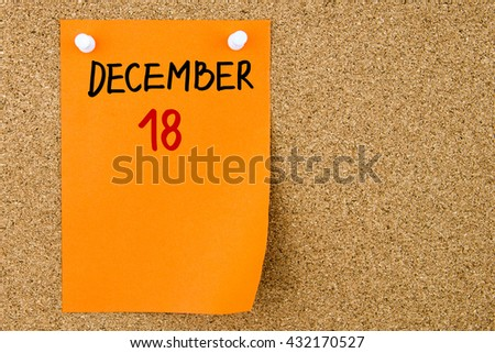 18 DECEMBER written on orange paper note pinned on cork board with white thumbtacks, copy space available - stock photo